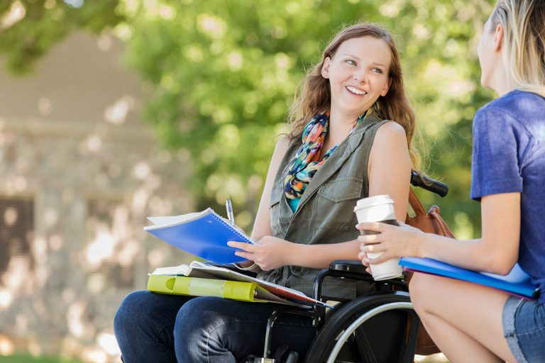 Woman with work folders using a wheelchair.