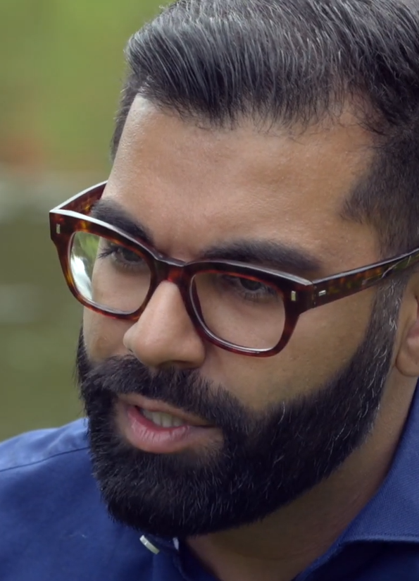 Image of Tarang Chawla, he has a dark beard and tortoiseshell glasses and a blue shirt. He's looking away from the camera and speaking.