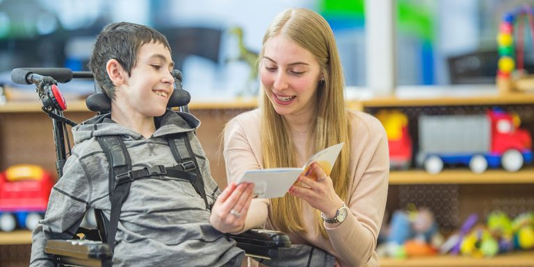 A teacher shows a document to a student who uses a wheelchair. They are both smiling.