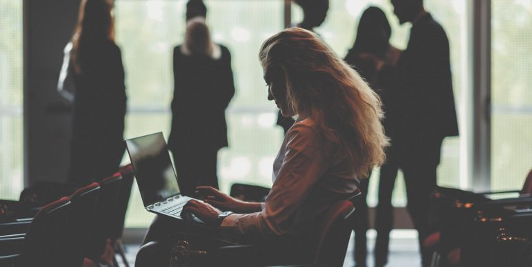 Shillouetted woman sitting in conference room looking at her laptop. She has long hair and there a people standing around talking in the background.