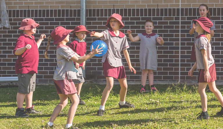 Primary school aged children in school uniform and sunhats playing with a ball in a school playground.