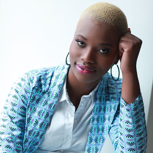 Our Watch ambassador Khadija Gbla is sitting and looking at the camera. She has brown skin, blond short hair and is wearing a blue blazer and white shirt.