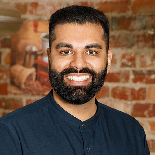Portrait of Tarang Chawla. He has dark hair and a dark beard, and is wearing a dark blue shirt. He's standing against a brick wall and smiling at the camera.