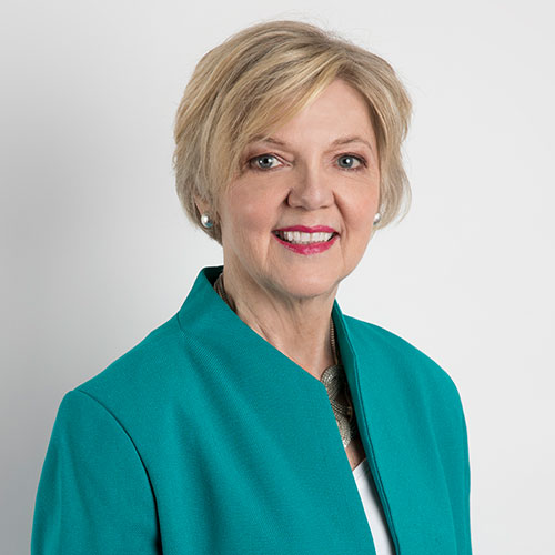 Portrait of Kerry Chikarovski. She has short blond hair and red lipstick and is smiling at the camera. She's wearing a teal coloured jacket.