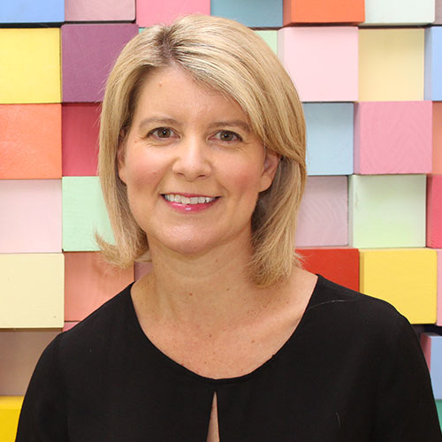 Portrait of Natasha Stott-Despoja. She has blond hair and brown eyes and is standing in front of a colourful wall. She is wearing a black top and smiling at the camera.