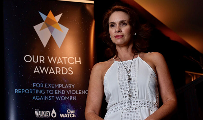 A woman with brown hair and a white top stands next to an Our Watch Awards banner. She's lit in orange light and is looking to the right of the camera.