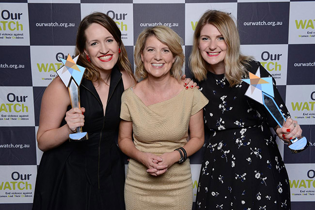 Three smiling women in front of an Our Watch media wall, two are holding awards they have just recieeved.
