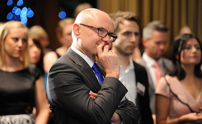 Man in a suit and a bald head and glasses has his hand to his chin thoughtfully and his head tipped to the side, listening. He is in a crowd of people dressed formally. The camera sees him from his right side.