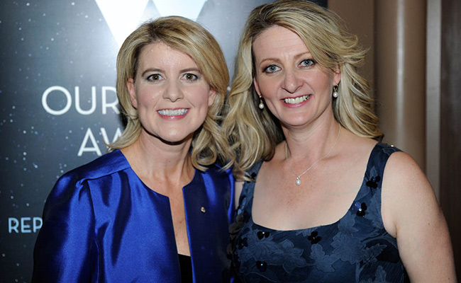 Two women stand smiling in front of an Our Watch Awards banner. They both have medium length blond hair and are wearing formal clothes.