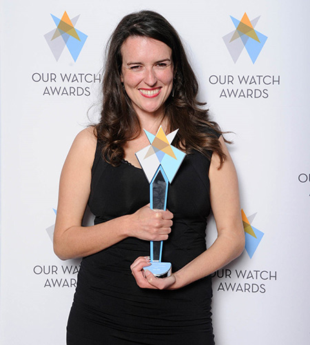 A woman in a black formal dress stands in front of an Our Watch Awards banner holding an award.