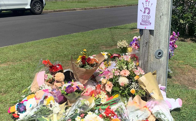 Makeshift memorial at Camp Hill with flowers piled at the base of a power pole.