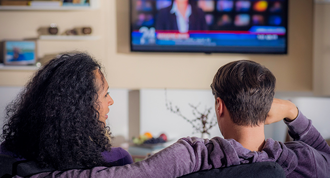 Woman and man watching news on TV.