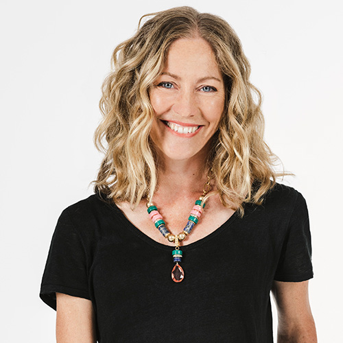 Photo of ambassador Tiffany Cherry. She has wavy blond hair, a black t shirt and colourful necklace. She is smiling at the camera.