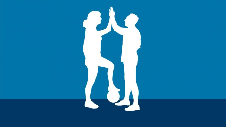 Silhouette of a woman and man doing a high five. The woman has her left foot rested on a round ball.