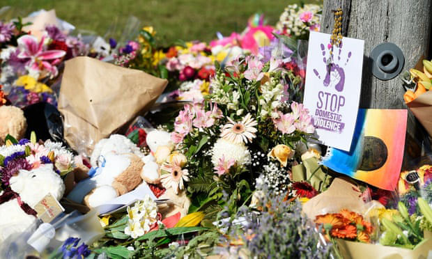 Memorial with flowers and poster that says 'Stop domestic violence'.